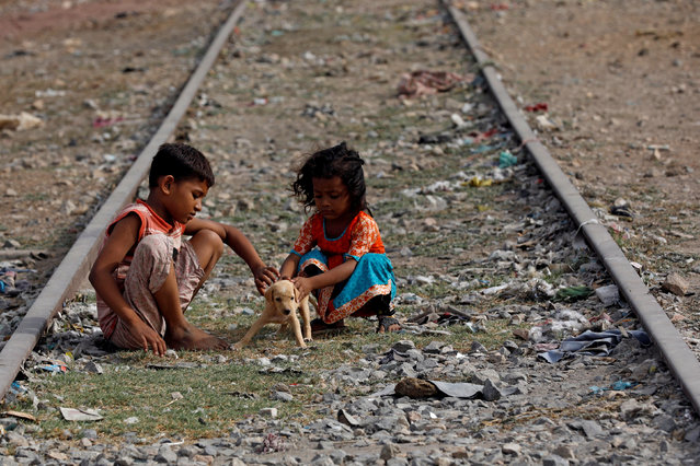 Siblings play with a puppy named Tiger along an old railway track in a low-income neighborhood in Karachi, Pakistan on August 6, 2018. (Photo by Akhtar Soomro/Reuters)