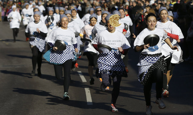 Competitors compete in the Olney 2015 pancake race in Olney, Buckinghamshire in England Tuesday, February 17, 2015. A pancake race has been run in the town since 1445 to mark the start of Lent. (Photo by Kirsty Wigglesworth/AP Photo)