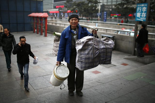 Shao Ju poses for a portrait at the Shanghai Railway station in Shanghai, February 12, 2015. Shao travelled to Sixian, in Anhui province, by train to spend Chinese New Year with his family. (Photo by Carlos Barria/Reuters)