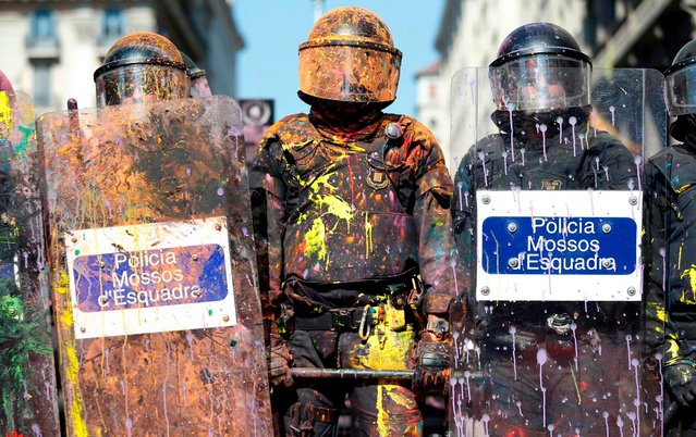 """Catalan regional police """"Mossos D"""" Esquadra' officers covered in paint stand guard after clashing with separatist protesters during a counter- protest against a demonstration in support of Spanish police in Barcelona on September 29, 2018. Monday, October 1, will mark one year since a banned independence referendum in Catalonia which was met with a massive police crackdown, captured the world' s attention and plunged Spain into its worst political crisis in decades. (Photo by Pau Barrena/AFP Photo)"""