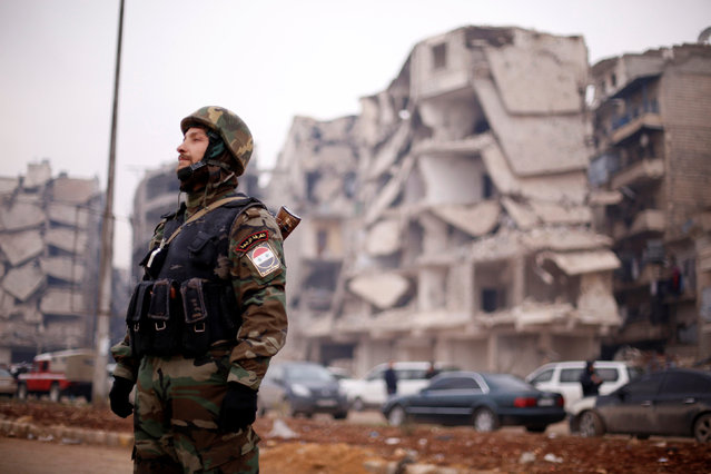 A member of forces loyal to Syria's President Bashar al-Assad stands near damaged buildings in Aleppo's Salaheddine district, Syria December 16, 2016. (Photo by Omar Sanadiki/Reuters)