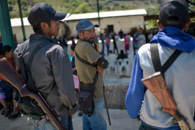 """People queue to cast their votes while community policing stand guard at a polling station in Nahuat community of Ayahualtempa, Guerrero state, Mexico, on June 6, 2021. Mexicans began voting Sunday in elections seen as pivotal to President Andres Manuel Lopez Obrador's promised """"transformation"""" of a country shaken by the coronavirus pandemic, a deep recession and drug-related violence. (Photo by Pedro Pardo/AFP Photo)"""