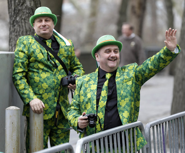 Neil Martin, right, and Martin Brown, both from Belfast, Ireland, watch the St. Patrick's Day Parade in New York, Tuesday, March 17, 2015. (Photo by Seth Wenig/AP Photo)