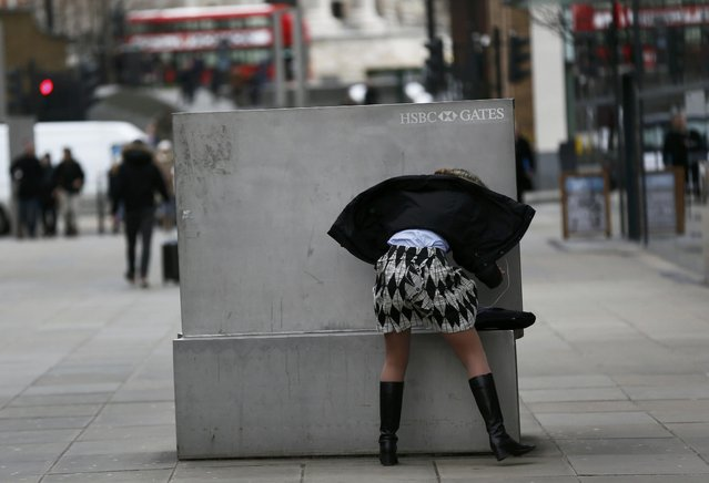 A woman shelters behind a bench during a windy day in London, Britain January 26, 2016. (Photo by Stefan Wermuth/Reuters)