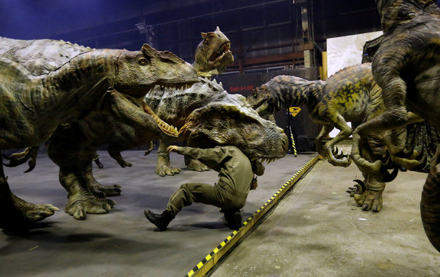 "Japan's ON-ART Corp's eight metre tall man-operated walking dinosaur robot ""TRX03"" (C) performs with and other robots at the company's studio in Tokorozawa, Japan, December 6, 2016. (Photo by Toru Hanai/Reuters)"