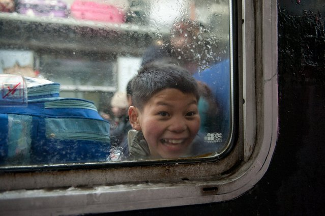 A boy looks out from a train window at Beijing Railway station, China, January 23, 2016. According to traffic police, over 2.9 billion trips will be made around China during the 40-day Spring Festival travel rush, which started on January 24. (Photo by Reuters/Stringer)