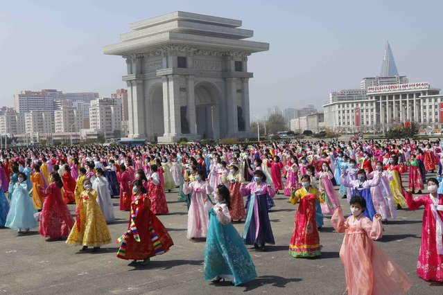 Women dance near the Arch of Triumph on the Day of the Sun, the birth anniversary of late leader Kim Il Sung, in Pyongyang, North Korea Thursday, April 15, 2021. (Photo by Cha Song Ho/AP Photo)