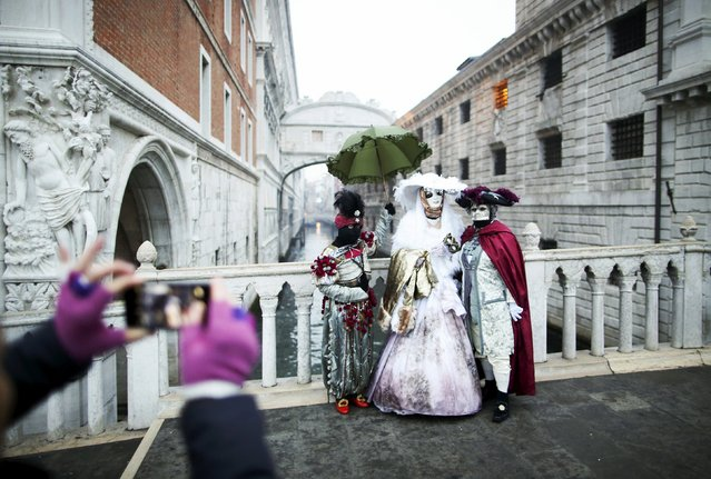 A tourist takes a picture of masked revellers (R) standing in front of the Ponte dei Sospiri (Bridge of Sighs) during the Venice Carnival January 30, 2016. (Photo by Alessandro Bianchi/Reuters)