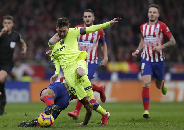 Barcelona's Lionel Messi, front right, duels for the ball with Athletico Madrid's Rodri during a Spanish La Liga soccer match between Atletico Madrid and FC Barcelona at the Metropolitano stadium in Madrid, Saturday, November 24, 2018. (Photo by Manu Fernandez/AP Photo)