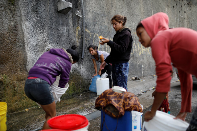 Women fill containers with water coming from a mountain, in a road at Plan de Manzano slum in Caracas, Venezuela July 20, 2018. Water cuts are the latest addition to a long list of woes for Venezuelans hurting from a fifth year of an economic crisis that has sparked malnutrition, hyperinflation and emigration. Malfunctions in the capital's water network due to lack of maintenance have taken a turn for the worst in recent months, depriving many in this city of 3 million people of regular running water. (Photo by Marco Bello/Reuters)