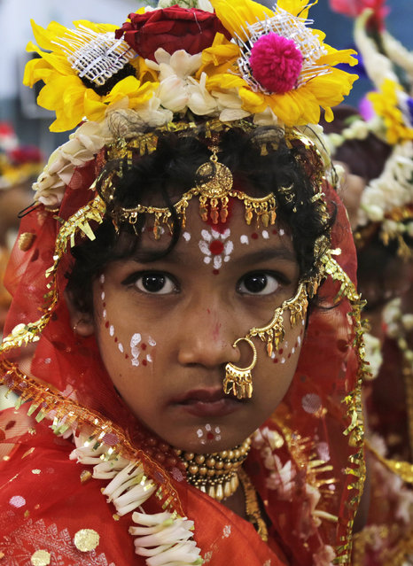 """A young Hindu girl sits for a ceremony where she and other girls are worshipped as """"Kumari"""", or living goddess, during Ram Navami festival, at a temple in Kolkata, India, Saturday, March 28, 2015. (Photo by Bikas Das/AP Photo)"""