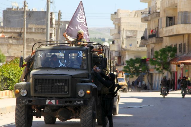 Nusra Front fighters ride a military vehicle that they seized from forces loyal to Syria's president Bashar Al-Assad in Jisr al-Shughour town after rebels took control of the area April 25, 2015. (Photo by Ammar Abdullah/Reuters)