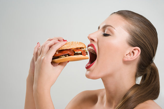 Young woman eating a burger. (Photo by Getty Images/Image Source)