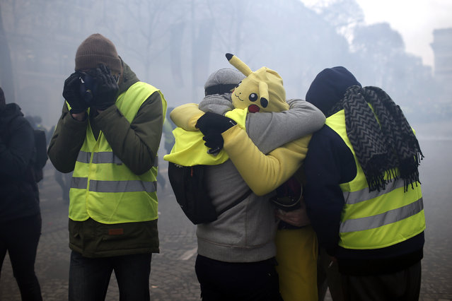 Demonstrators wearing yellow vests protect their eyes amid tear gas on the Champs-Elysees avenue Saturday, December 8, 2018 in Paris. (Photo by Rafael Yaghobzadeh/AP Photo)