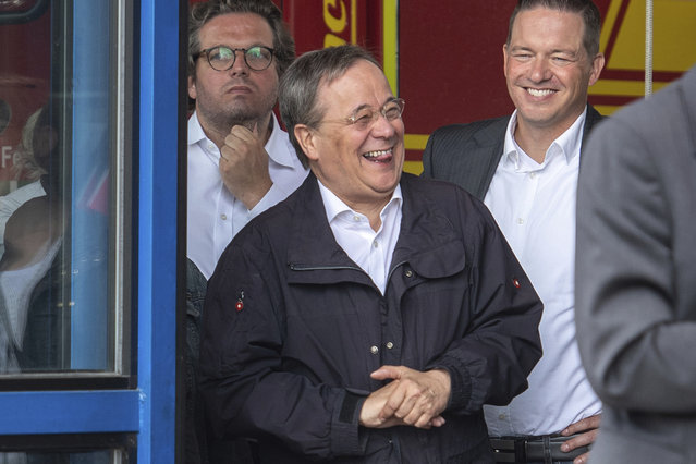 Armin Laschet, center, Governor of the German state of North Rhine-Westphalia and the top candidate of the German Christian Democrats for the upcoming federal elections, laughs in Erftstadt, Germany, Saturday, July 17, 2021 while German President Steinmeier gives a press statement on the floodings in Germany. (Photo by Marius Becker/dpa via AP Photo)