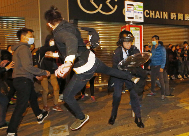 A protester kicks a riot police in Mong Kok district of Hong Kong, Tuesday, February 9, 2016. Hong Kong's Lunar New Year celebration descended into chaotic scenes as protesters and police, who fired warning shots into the air, clashed over a street market selling fish balls and other local holiday delicacies, leaving dozens injured and arrested. (Photo by Kin Cheung/AP Photo)