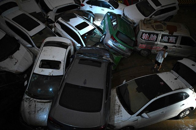 A man smokes a cigarette near cars stacked on each other at an entrance of a tunnel  following a heavy rain in Zhengzhou in China's Henan province on July 21, 2021. (Photo by Noel Celis/AFP Photo)