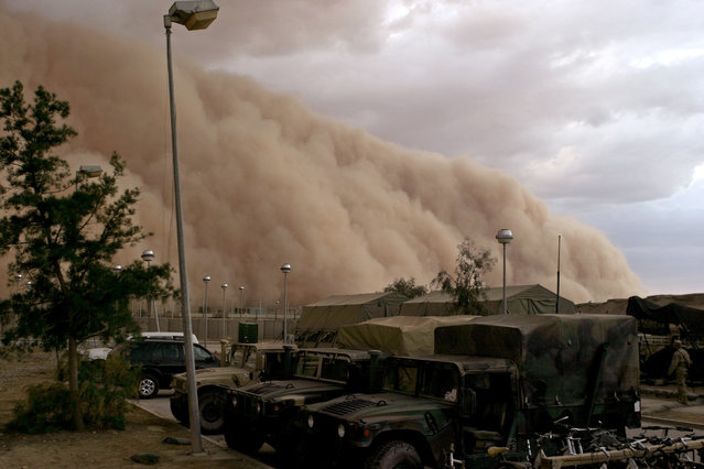 A massive sand storm cloud is close to enveloping a military camp as it rolls over Al Asad, Iraq, April 27, 2005. (Photo by Cpl. Alicia M. Garcia, U.S. Marine Corps/Reuters/U.S. Department of Defense)