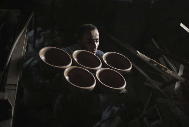 A Palestinian worker carries newly made pottery, to be dried at pottery workshop in Gaza City, Sunday, November 20, 2016. (Photo by Khalil Hamra/AP Photo)