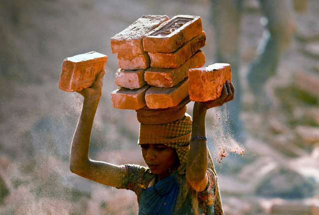 An Indian migrant laborer girl works at a brick factory in Lalitpur, Nepal, April 1, 2015. Thousands of Indian and Nepali seasonal migrant laborers each year come to work at brick factories around the Kathmandu valley during winter and spring seasons. (Photo by Narendra Shrestha/EPA)