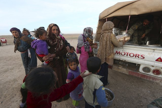 Fighters from the Democratic Forces of Syria distribute food aid to internally displaced Syrians that fled the town of Sabaa Zlam in the southwestern countryside of Hasaka, Syria February 17, 201. (Photo by Rodi Said/Reuters)