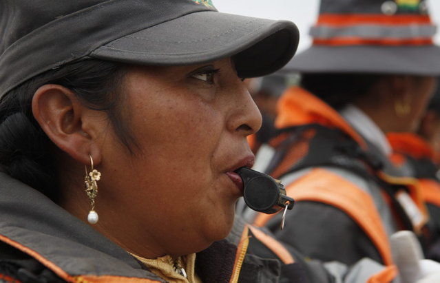 In this December 13, 2013 photo, an Aymara traffic policewomen learns to use a whistle to control and direct traffic during a training session in El Alto, Bolivia. (Photo by Juan Karita/AP Photo)