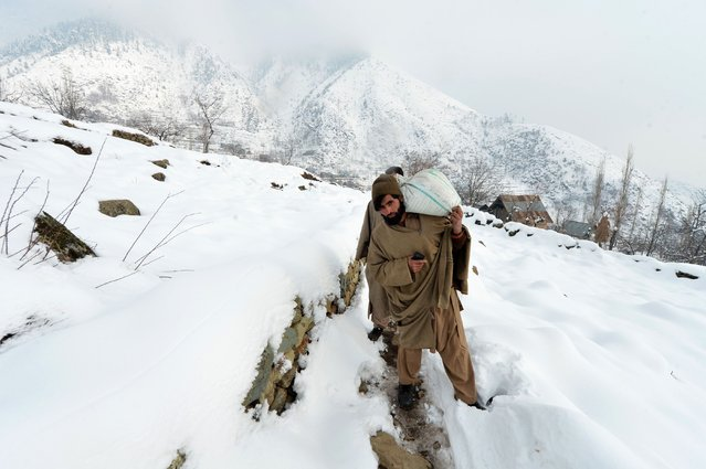 A Kashmiri Muslim villager walks towards home as he carries a rice bag along a snow-covered road  on the outskirts of Srinagar on January 13, 2017. A cold wave further tightened its grip in Jammu and Kashmir with most places in the state recording sub-zero temperatures. The icy temperatures have frozen many bodies of water in Kashmir as well as drinking water taps. (Photo by Tauseef Mustafa/AFP Photo)