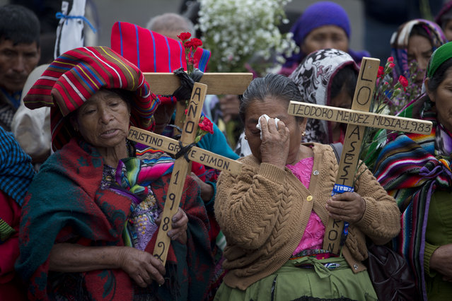 """Indigenous women pray holding wooden crosses during a ceremony by human rights activists in front of the Supreme Court in Guatemala City, Thursday, February 25, 2016. Guatemalans commemorate the """"National Day of Dignity for the Victims of Armed Internal Conflict"""" every Feb. 25 in honor of the victims of the civil war that ended in 1996. (Photo by Moises Castillo/AP Photo)"""