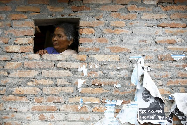 A woman looks towards the chariot of Rato Machhindranath from the window of a house during the chariot festival at Bungamati in Lalitpur April 22, 2015. (Photo by Navesh Chitrakar/Reuters)