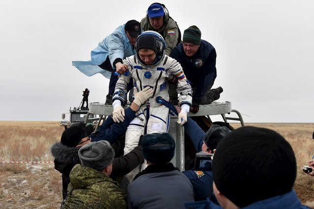Ground personnel help Russian cosmonaut Sergei Volkov to get out of a Soyuz capsule shortly after landing near the town of Dzhezkazgan (Zhezkazgan), Kazakhstan, March 2, 2016. (Photo by Kirill Kudryavtsev/Reuters)