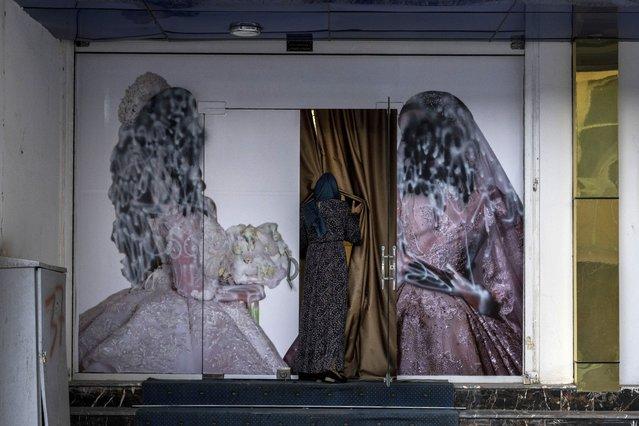 An Afghan woman enters a beauty salon in Kabul, Afghanistan, Saturday, September 11, 2021. (Photo by Bernat Armangue/AP Photo)
