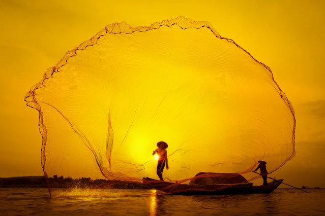 """Catch the sunset"". Vietnam. A fishermen tosses his net. (Photo by Tuan Nguyen Manh)"