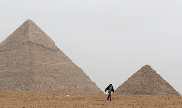 A man walks in front of the Great Pyramids in Giza, on the outskirts of Cairo, Egypt February 15, 2019. (Photo by Mohamed Abd El Ghany/Reuters)