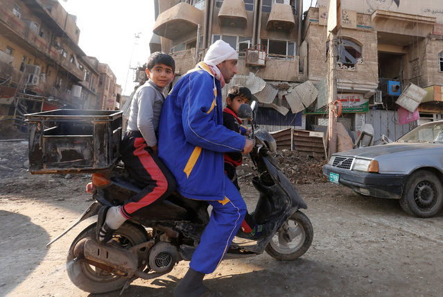 A man rides a motorbike with his children at al Zohour area in Mosul, Iraq, January 23, 2017. (Photo by Muhammad Hamed/Reuters)