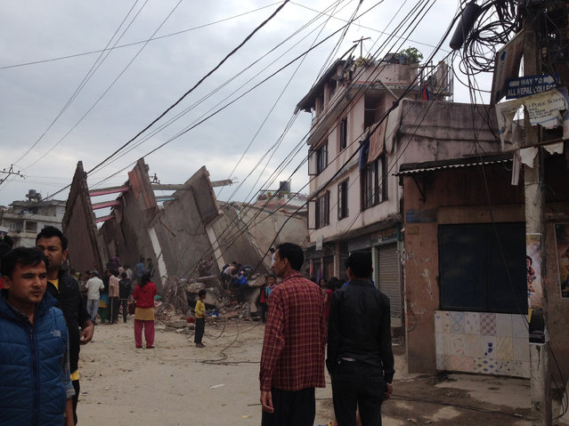 In this photo provided by Guna Raj Luitel, people walk next to ruble after an earthquake in Kathmandu, Nepal, Saturday, April 25, 2015. (Photo by Guna Raj Luitel/AP Photo)