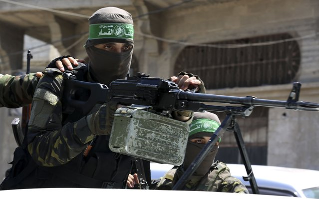 A masked militant from the Izzedine al-Qassam Brigades, a military wing of Hamas, stands behind a machine gun on a truck as mourners carry the body of Osama Dueij, 32, who was shot in the leg on Saturday during a violent demonstration on the northern border between Gaza and Israel, during his funeral procession in Jebaliya refugee camp, northern Gaza Strip, Wednesday, August 25, 2021. (Photo by Adel Hana/AP Photo)