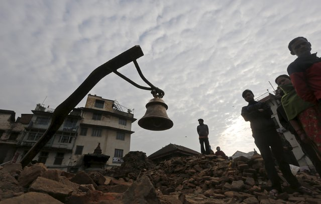 A prayer bell is seen on top of the rubble of a damaged temple after an earthquake in Kathmandu, Nepal April 28, 2015. (Photo by Adnan Abidi/Reuters)
