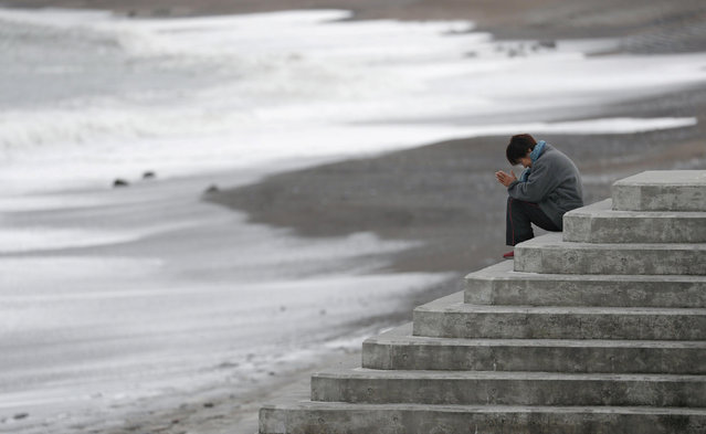 A woman faces the sea to pray while mourning the victims of the March 11, 2011 earthquake and tsunami disaster, in Iwaki, Fukushima prefecture, Japan on March 11, 2019. (Photo by Kyodo News via Reuters)