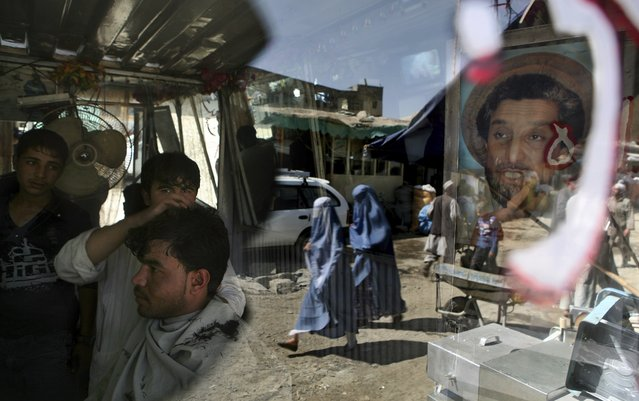 An Afghan barber works on a customer in his shop as a portrait of Afghanistan national hero Ahmad Shah Massoud adorns its door in Kabul, Afghanistan, Tuesday, September 29, 2009. (Photo by Altaf Qadri/AP Photo)