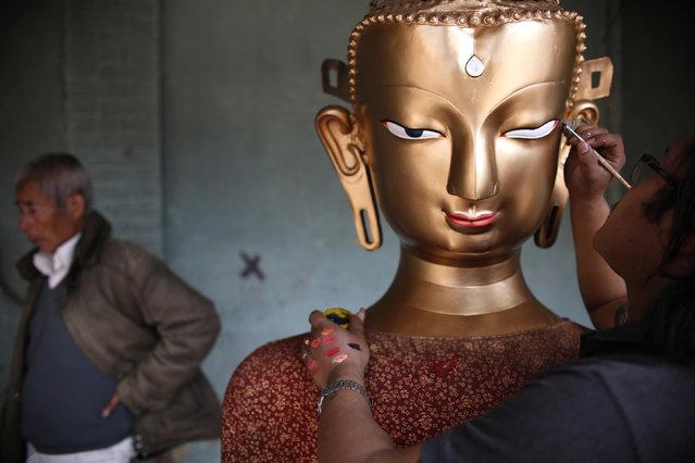 Saroj Shakya, 26, gives a finishing touch to an idol of Buddha ahead of the Samyak festival in Lalitpur, Nepal, March 11, 2016. (Photo by Navesh Chitrakar/Reuters)