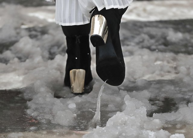 A woman walks through slush as she crosses the street on her way to a fashion show during Fashion Week, Thursday, February 9, 2017, in New York. (Photo by Julie Jacobson/AP Photo)