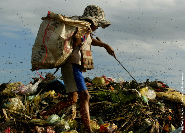 A Cambodian girl goes through the garbage dump looking for things to recycle in order to survive