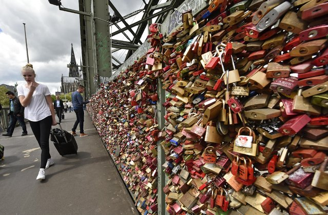People are passing love locks on the train bridge in Cologne, Germany, Tuesday, May 5, 2015. In a tradition lovers have put thousands of locks with their names on the railings and then threw the keys into the river Rhine to secure their love. (Photo by Martin Meissner/AP Photo)