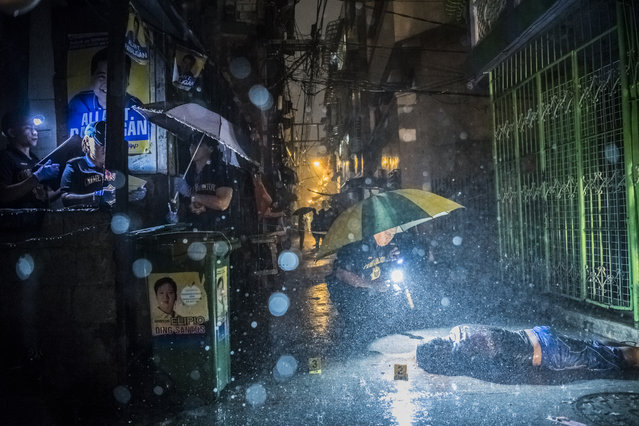 A handout photo made available by the World Press Photo (WPP) organization on 13 February 2017 shows a picture by The New York Times photographer Daniel Berehulak that won the General News – First Prize, Stories award of the 60th annual World Press Photo Contest, it was announced by the WPP Foundation in Amsterdam, The Netherlands on 13 February 2017. Caption: Heavy rain pours as police operatives investigate inside an alley where a victim, Romeo Joel Torres Fontanilla (37) was killed by two unidentified gunmen riding motorcycles in the early morning in Manila, Philippines. Story: President Rodrigo Duterte of the Philippines began his anti-drug campaign when he took office on 30 June 2016. Since then, more than 2,000 people have been slain at the hands of the police alone. Beyond those killed in official drug operations, the Philippine National Police have counted more than 3,500 unsolved homicides since 1 July. The victims, suspected users and pushers, are not afforded any semblance of due process. (Photo by Daniel Berehulak/EPA/The New York Times/World Press Photo)
