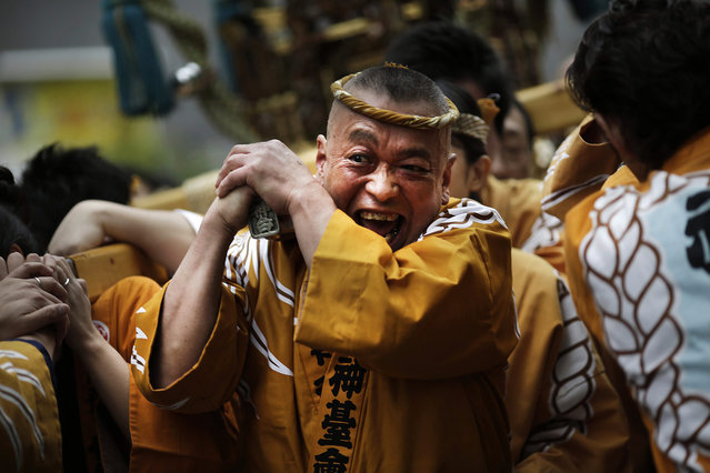 Carrying a portable shrine on their shoulders, participants all clad in traditional happi coats, parade through precincts of the Kanda Myojin shrine during the annual summer festival in Tokyo, Saturday, May 9, 2015. (Photo by Eugene Hoshiko/AP Photo)