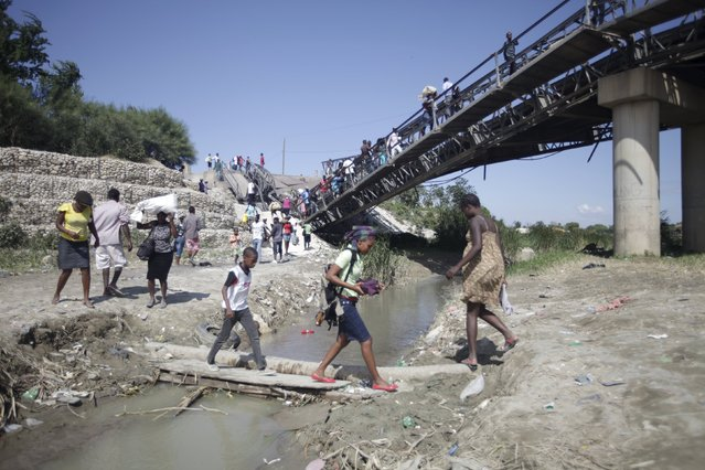 Haitians cross a river next to a collapsed bridge on the outskirts of Port-au-Prince, Haiti, March 24, 2016. (Photo by Andres Martinez Casares/Reuters)