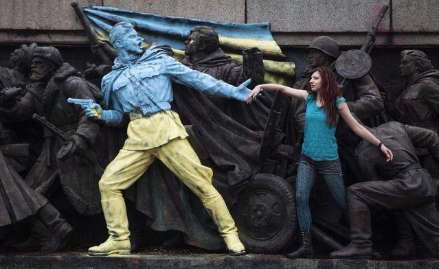 """A woman poses for a picture with the figures of Soviet soldiers at the base of the Soviet Army monument, parts of which have been painted in the colours of the Ukranian flag by an unknown person, in Sofia February 23, 2014. The Ukrainian flag and the statement """"Glory to Ukraine!"""" in Ukrainian was painted on an imposing Soviet Army Monument in Bulgarian capital Sofia overnight  as an artistic support for the struggle of the Ukrainian protesters to transform the former Soviet Republic. (Photo by Pierre Marsaut/Reuters)"""