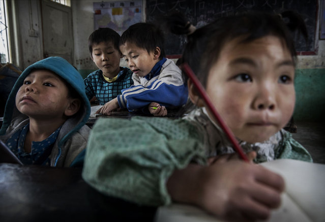 """""""Left behind"""" child Luo Lie, 5, background right, do schoolwork in class at a local school on December 16, 2016 in Anshun, China. (Photo by Kevin Frayer/Getty Images)"""