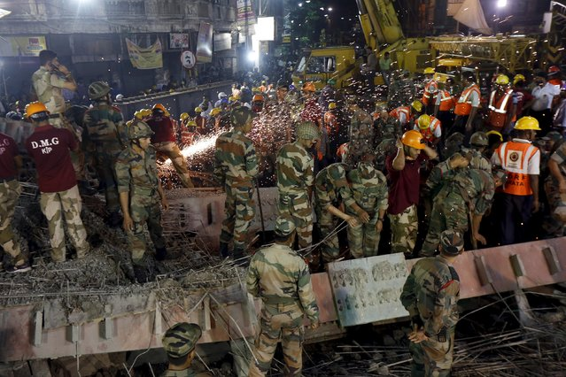 Firefighters, soldiers and rescue workers search for victims at the site of an under-construction flyover after it collapsed in Kolkata, India, March 31, 2016. (Photo by Rupak De Chowdhuri/Reuters)