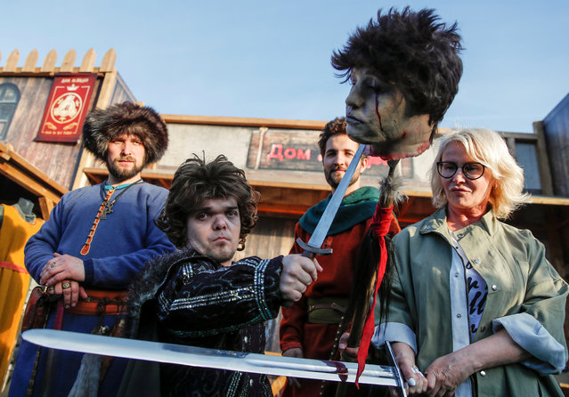 """An actor dressed as Tyrion Lannister, poses for photographers with fake severed head before the screening of final episode of """"Game of Thrones"""" on 20-meter-high screen at RZD Arena in Moscow, Russia on May 20, 2019. (Photo by Maxim Shemetov/Reuters)"""